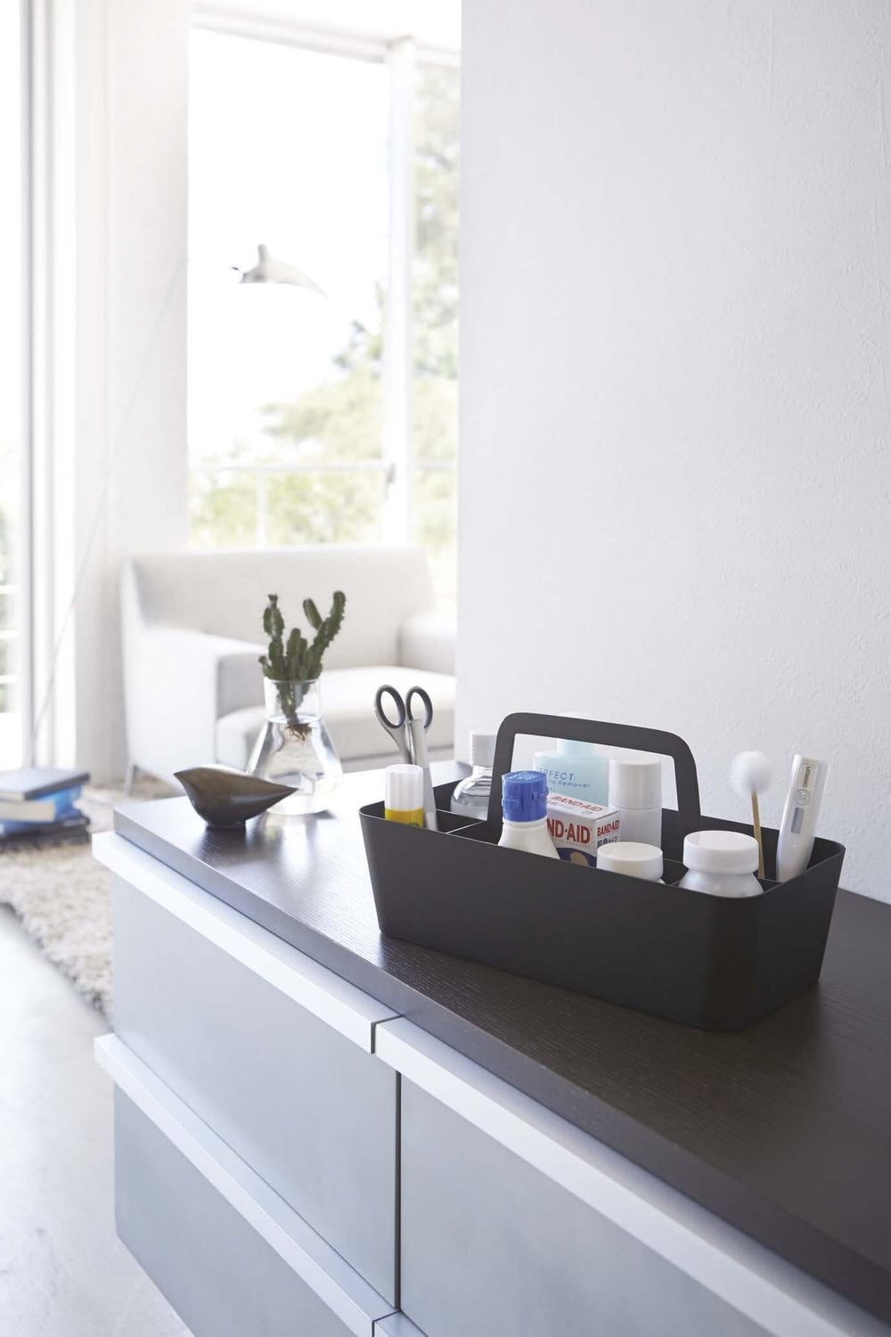 Large handled black storage caddy by Yamazaki, holding first-aid items sitting on a dresser.