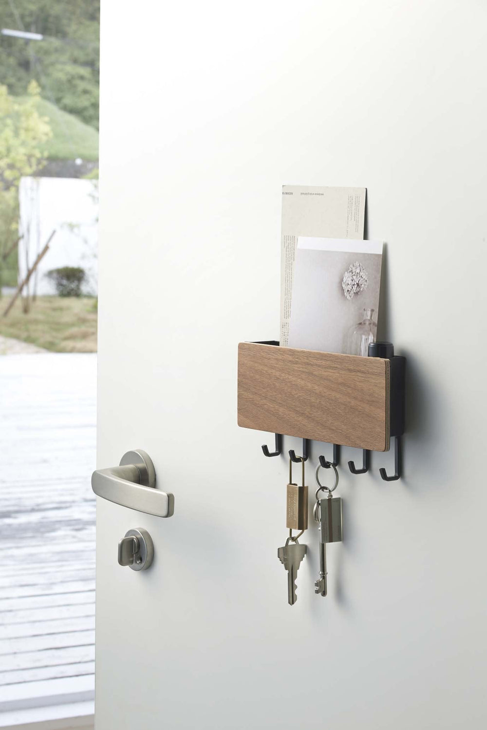 Yamazaki's magnetic key rack with wood front panel and five hooks holding mail and keys.
