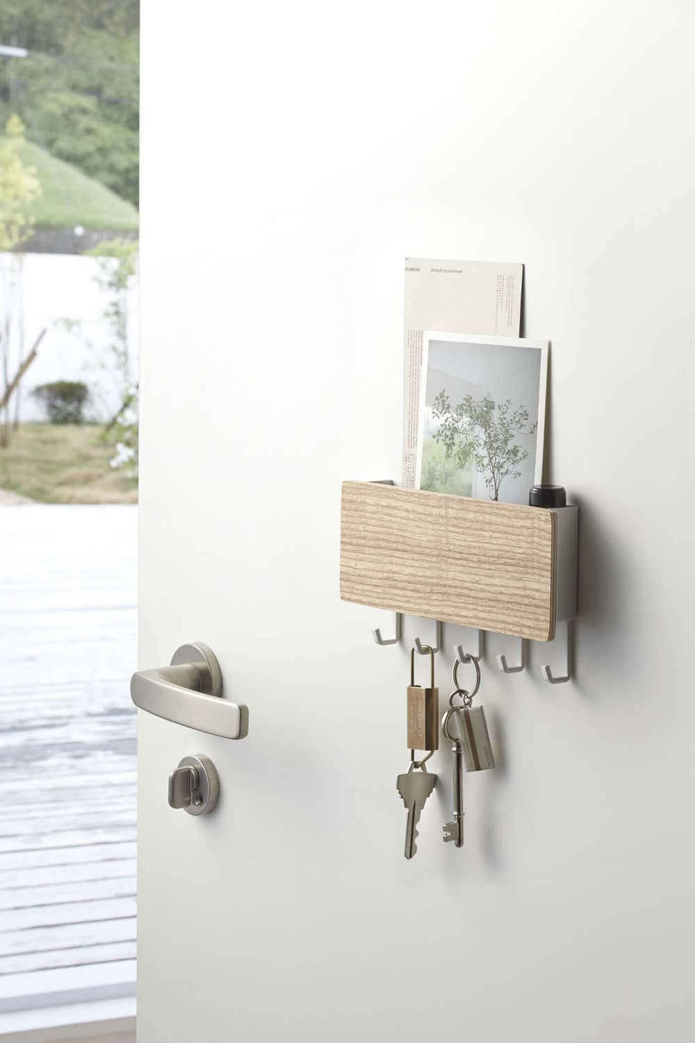 Yamazaki's magnetic key rack with wood front panel holding keys and postcards