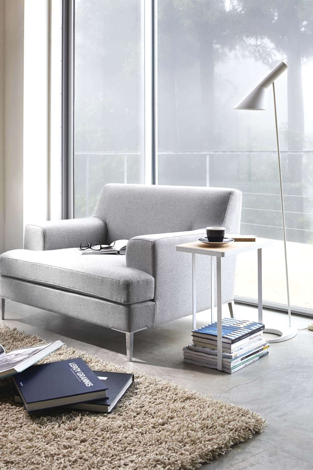 Yamazaki's White accent table stacked with magazines, positioned next to modern gray chair in a sunny room.