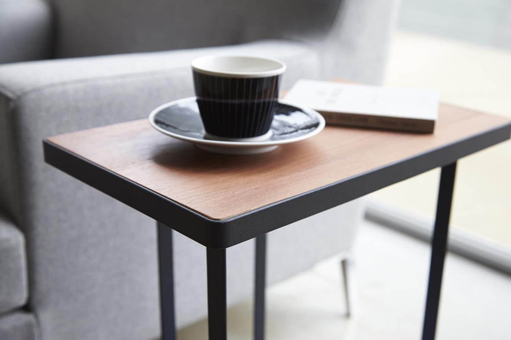 Detail of Yamazaki's black accent table with wood top, with a coffee cup sitting tabletop.