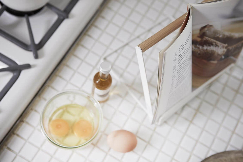 Yamazaki's White book stand holding book open on tiled kitchen counter next to baking ingredients.