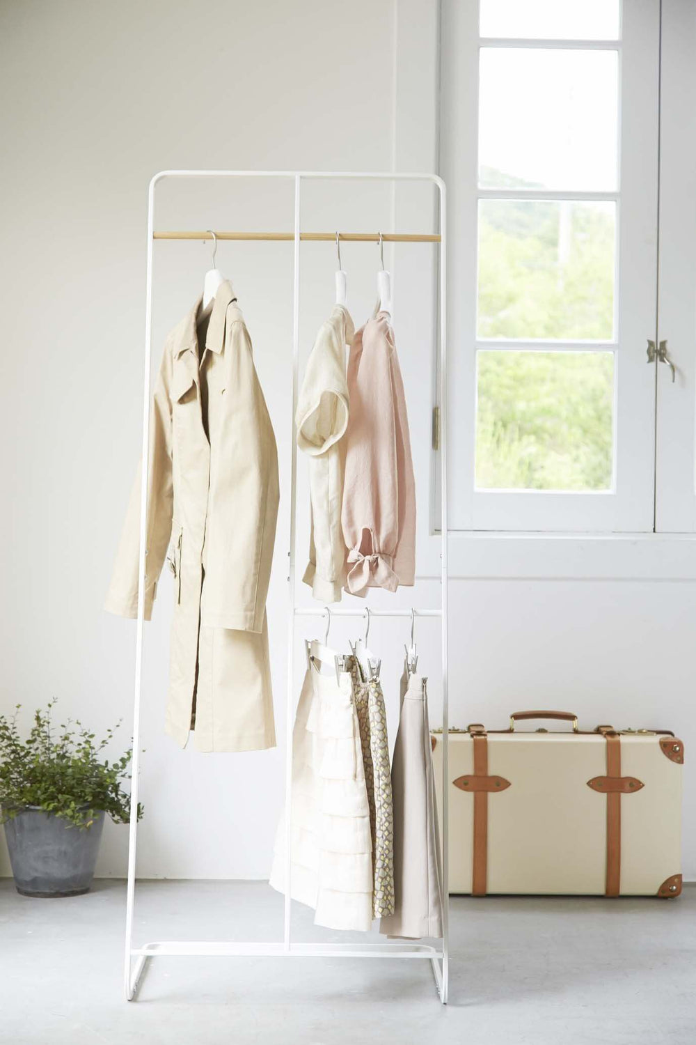 White 2-level coat rack by Yamazaki hung with clothes in room.