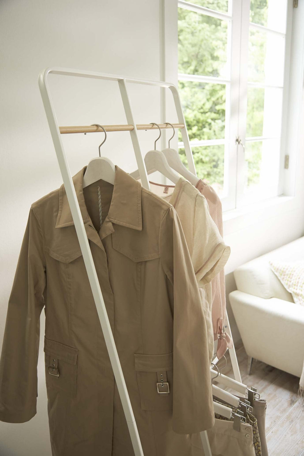 Close-up of white 2-Level Coat Rack by Yamazaki hung with clothes in a sunny room