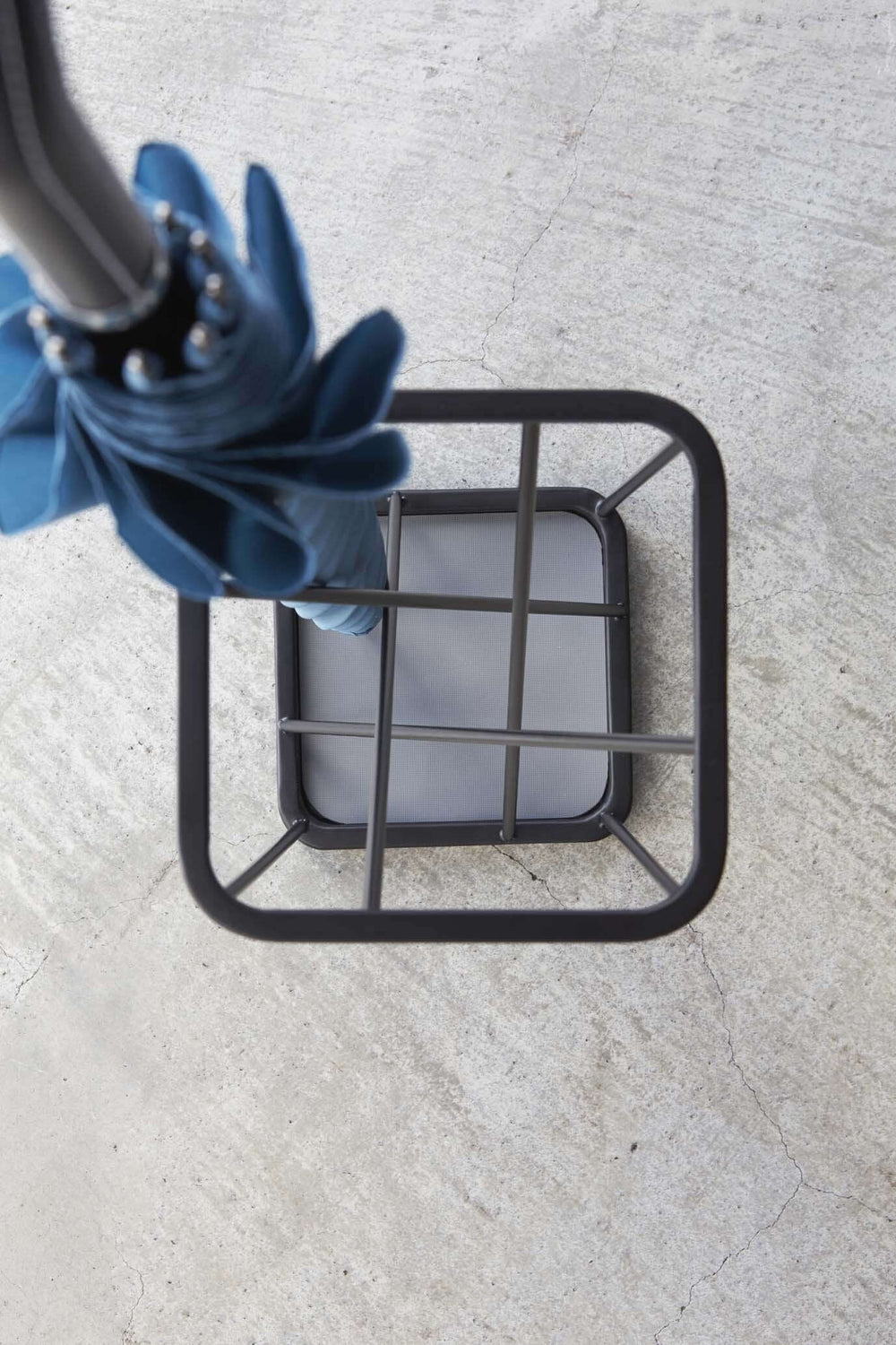 A Yamazaki umbrella stand designed with criss-crossing lines forms a nine-square grid when seen from above.