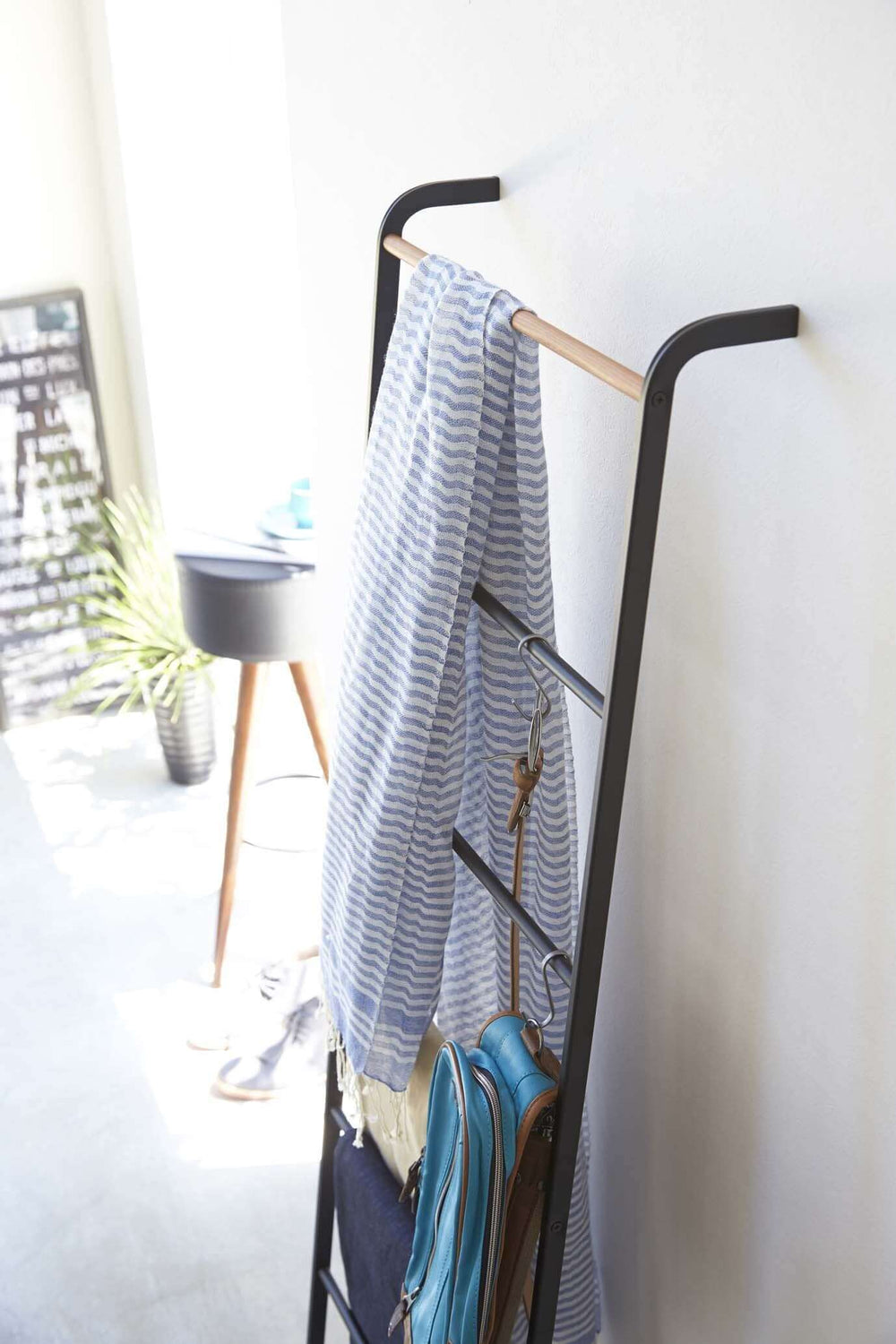 Yamazaki's black leaning ladder hung with scarves and bags in a bedroom