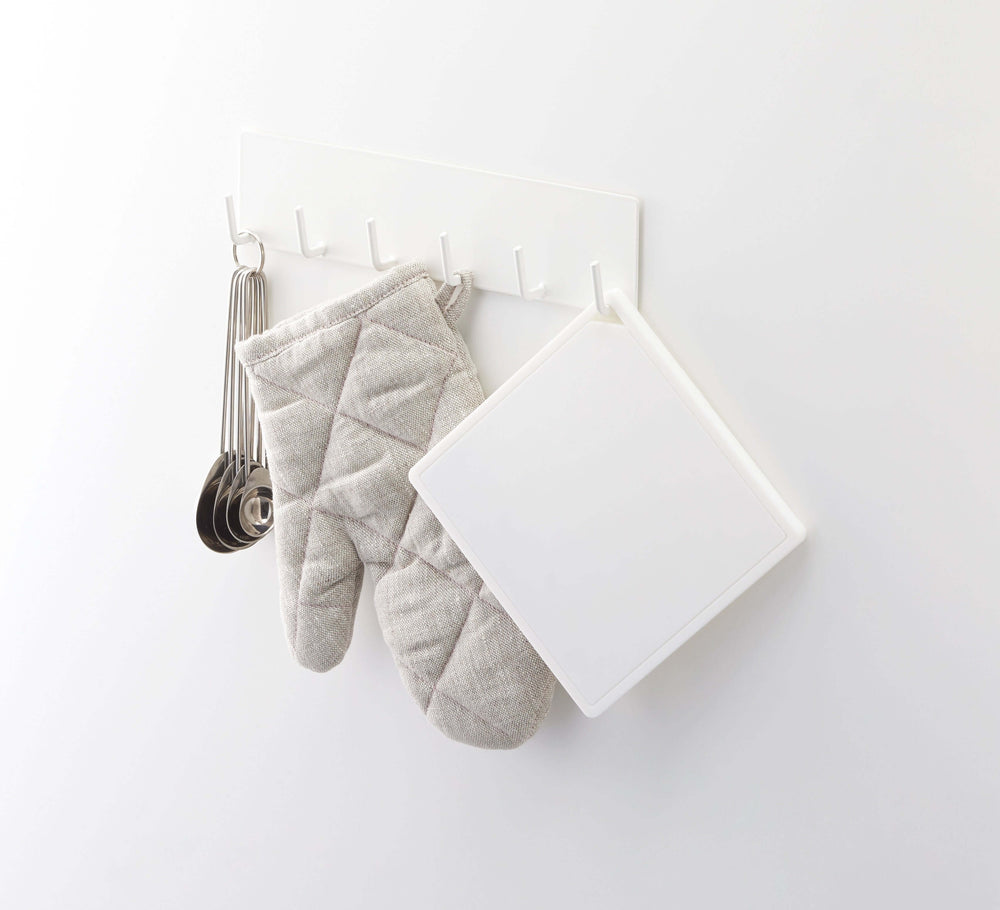 Yamazaki's square white silicone trivet hanging from kitchen rack