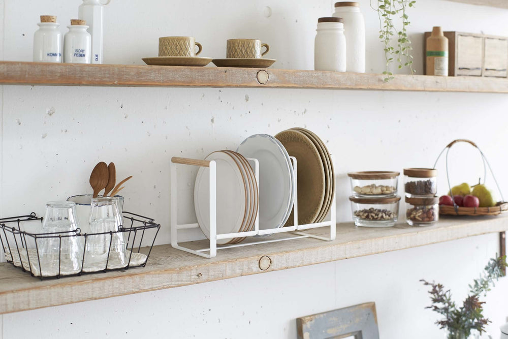 Yamazaki's white dish rack with wooden handles holding dishes on a kitchen shelf
