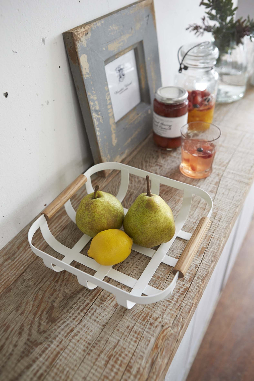 White basket by Yamazaki holding fruit on kitchen shelf