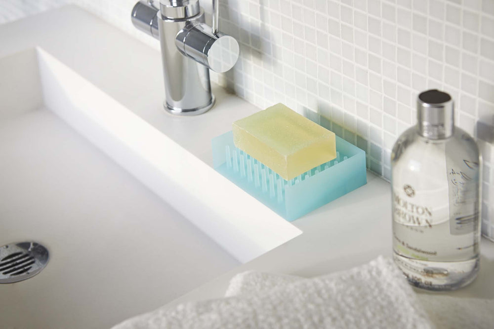 A bar of soap on the bathroom sink in a blue silicone Yamazaki soap dish.