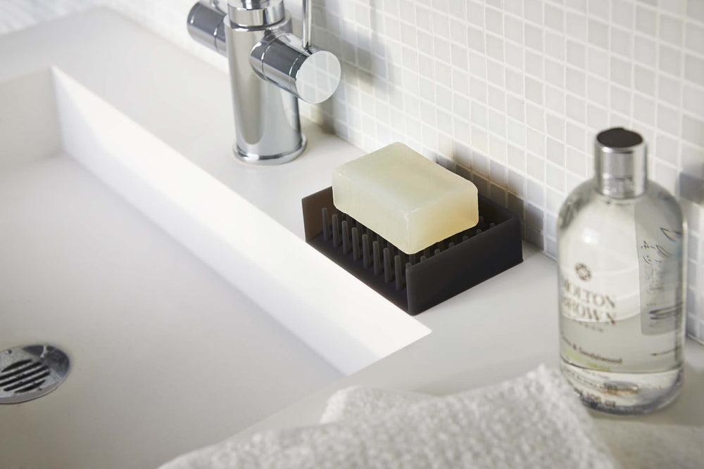 A bar of soap on the bathroom sink in a gray silicone Yamazaki soap dish.