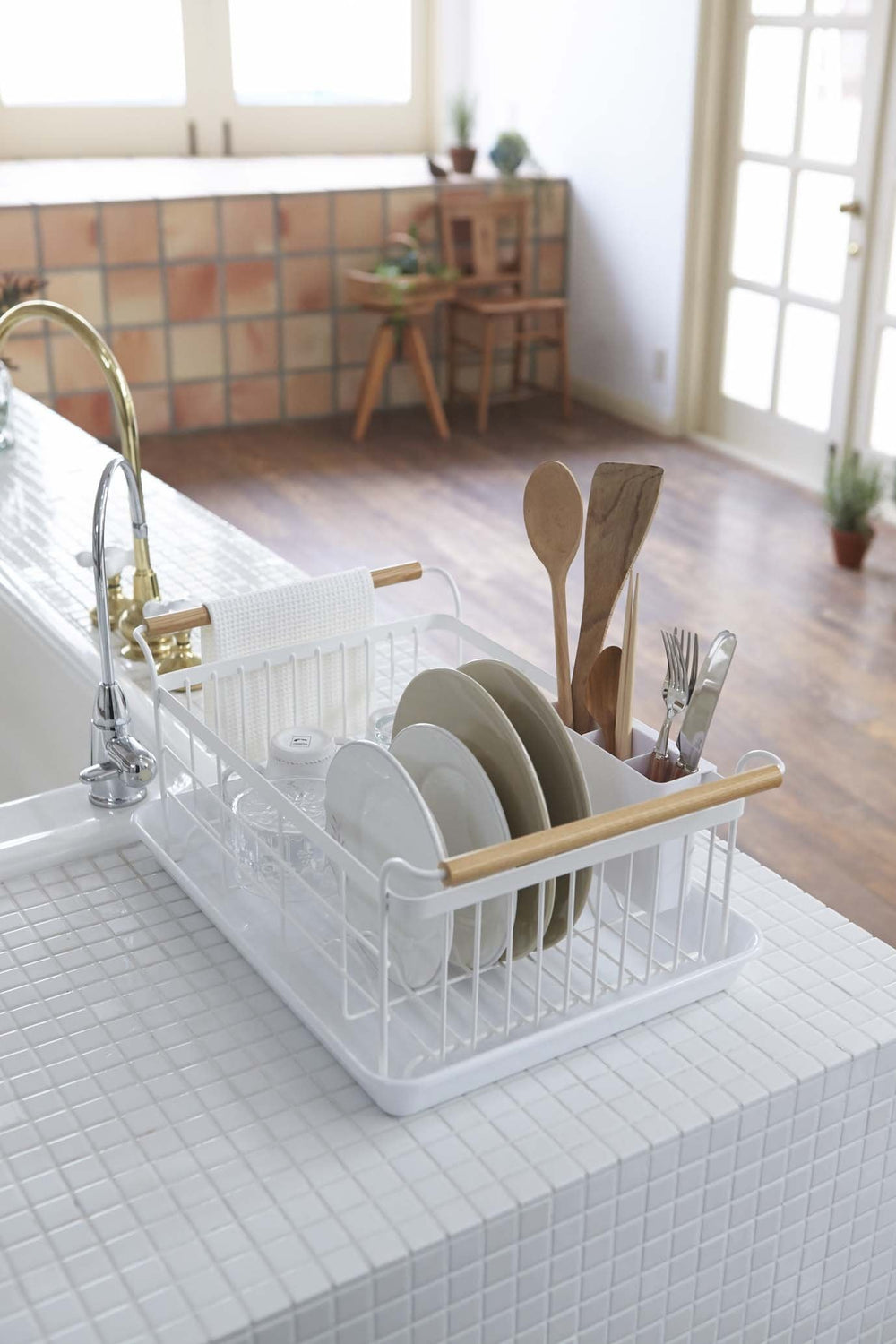 Yamazaki's dish rack styled after a basket with handles sitting next to sink on a tile countertop