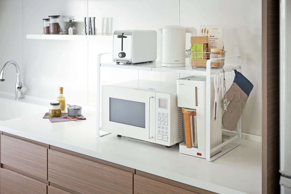 Yamazaki's white counter organizer sitting atop a microwave in a kitchen