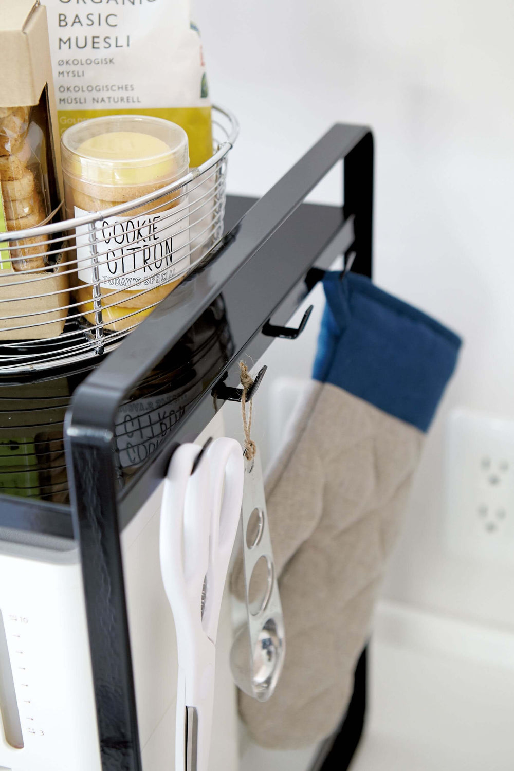 Scissors hanging from the side of a kitchen organizer by Yamazaki