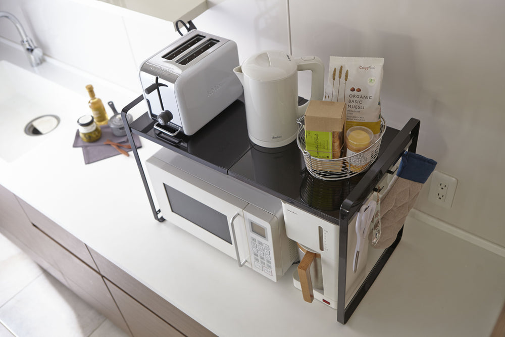 Counter organizer by Yamazaki sitting atop a microwave in a kitchen.