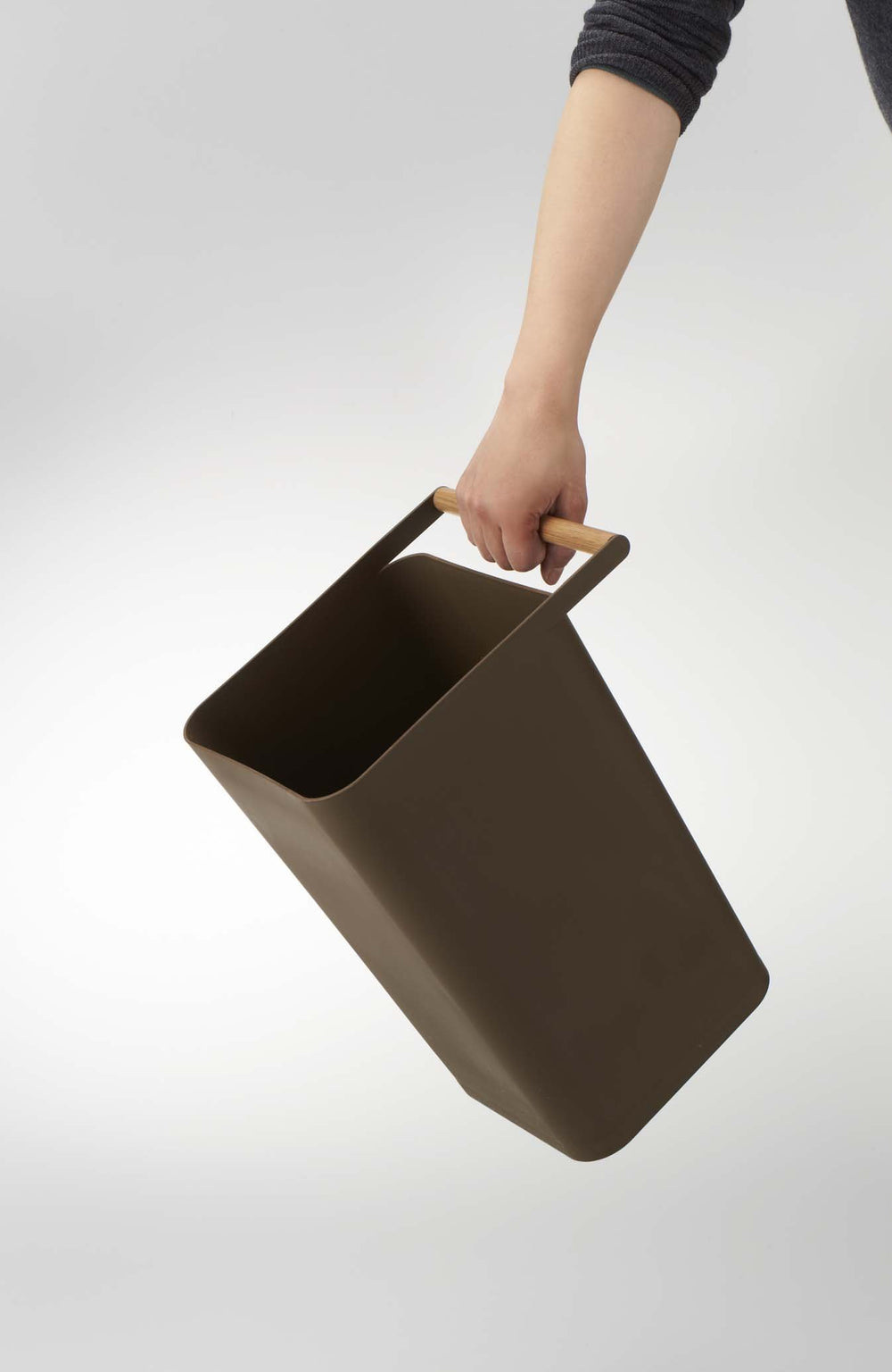 Someone carrying the Yamazaki wastebasket by the wooden handle.