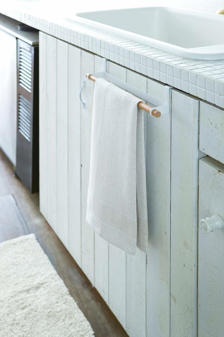 Yamazaki's wooden towel bar with white metal hooks hanging over bathroom cabinet door, holding a towel