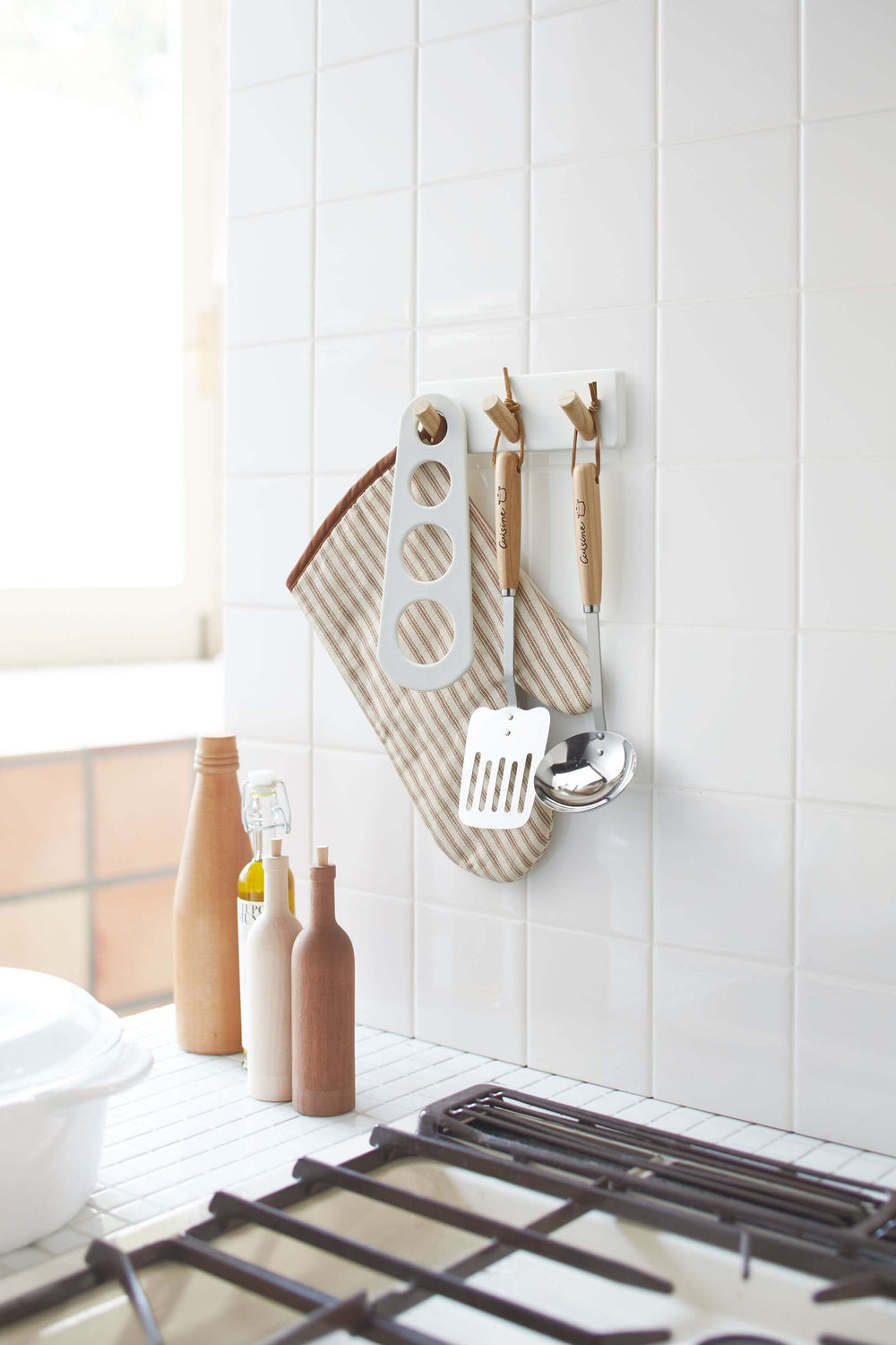 Yamazaki's magnetic peg rack holding cooking utensils above the sink.