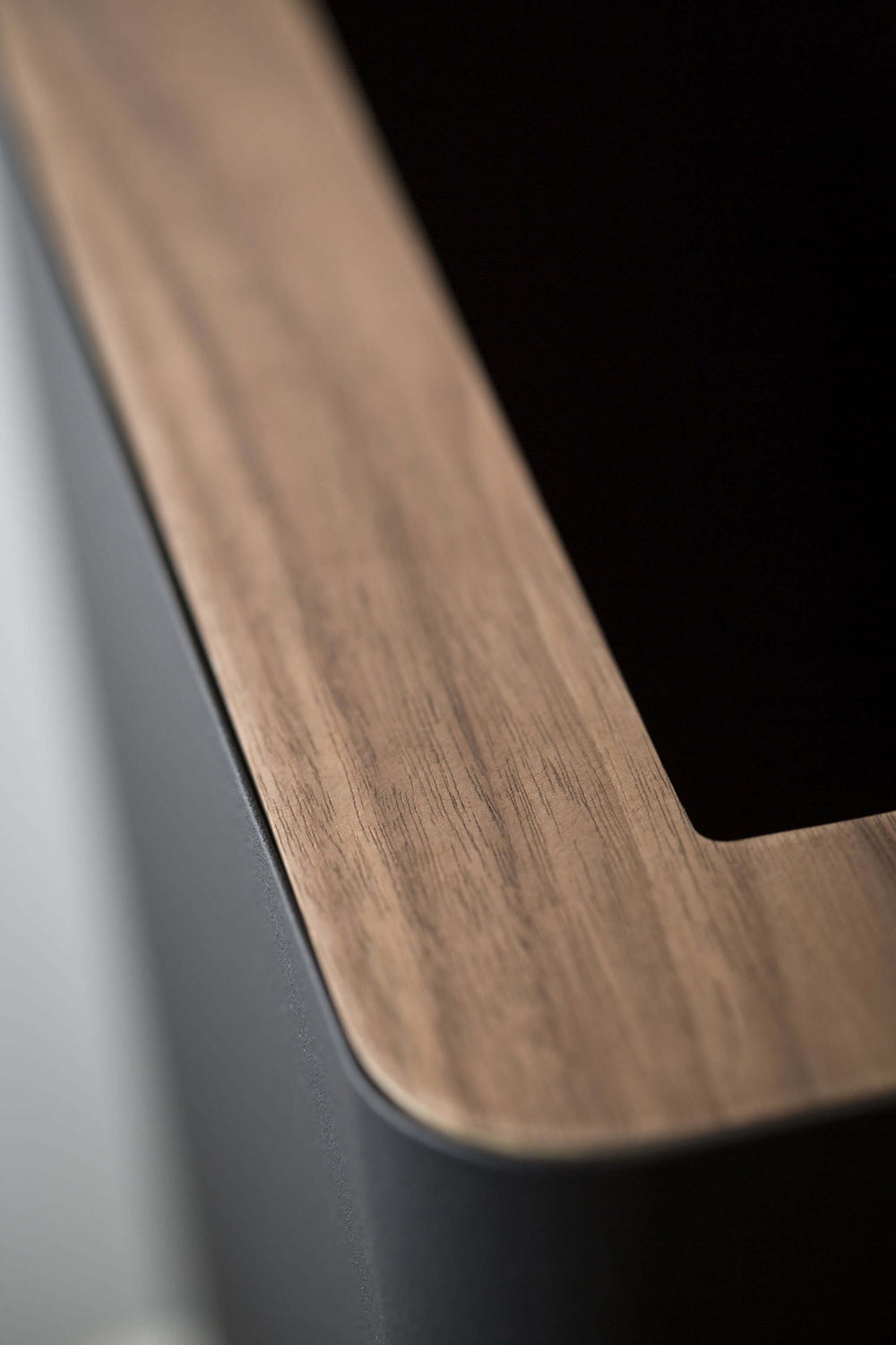 Close look at wooden top of Yamazaki's black rectangular trash can