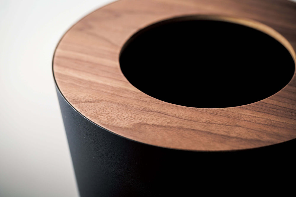 Close look at the wooden top of round black Yamazaki wastebasket.