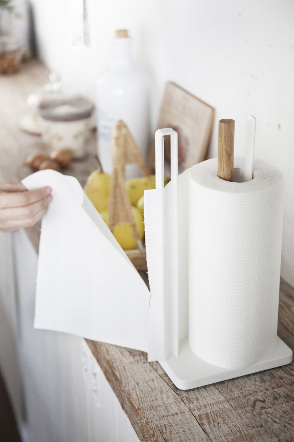 Tearing a paper towel with Yamazaki's standing paper towel holder with wooden rod and bar