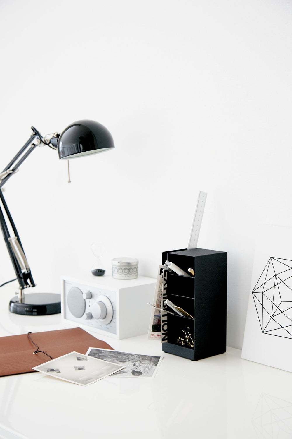 Yamazaki's Black 4 Tiered Desk Organizer positioned on an artfully cluttered white desk