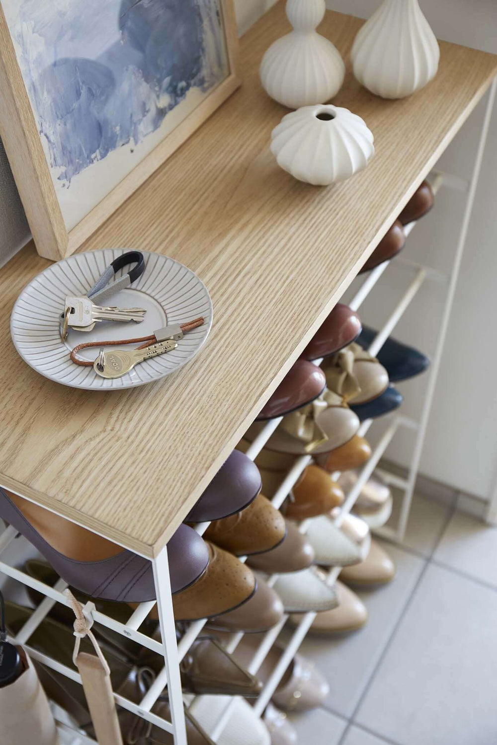 Aerial view of Yamazaki's white 6 Tier Wood Top Shoe Rack with keys, vases and artwork on the top wooden shelf