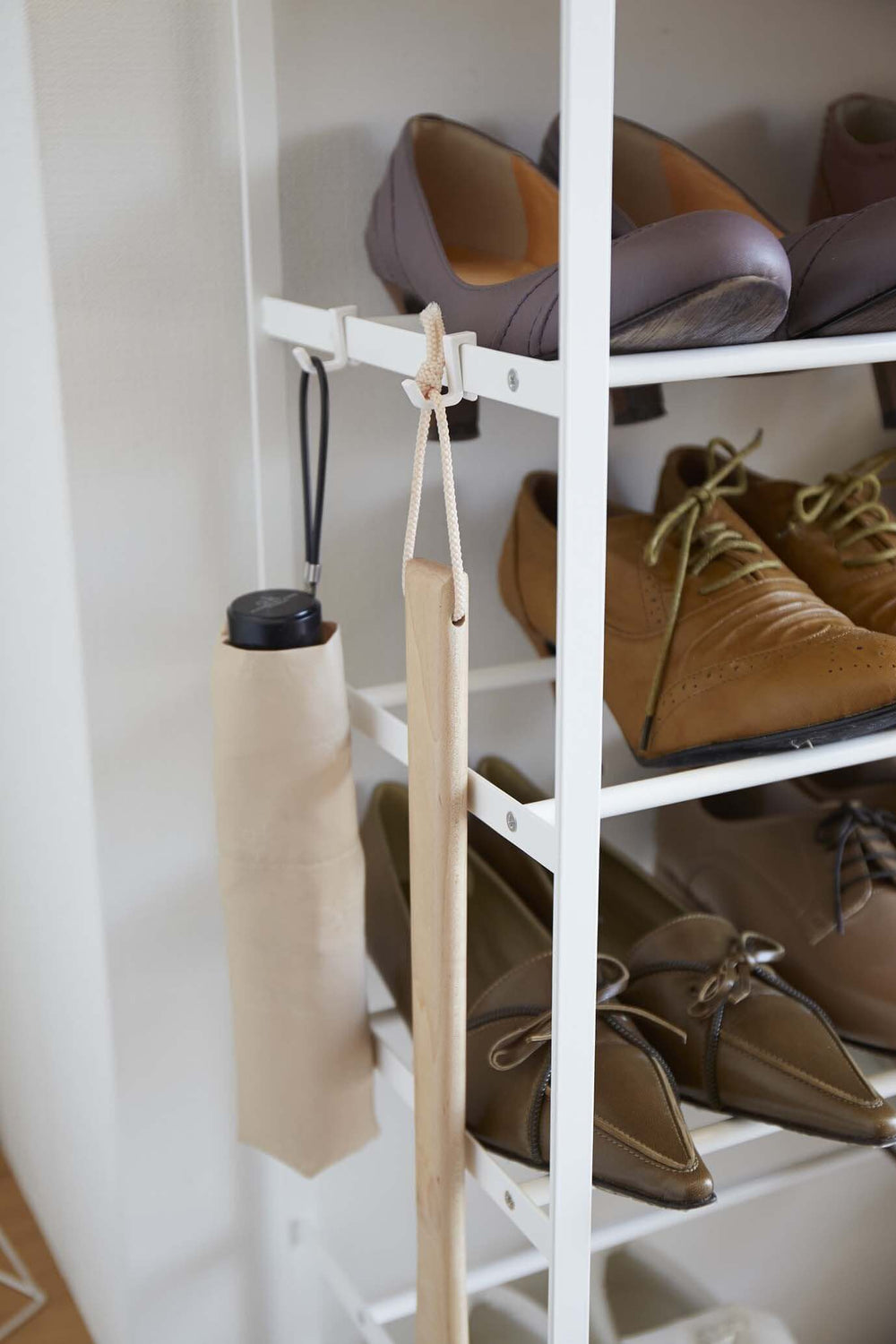 Detail of Yamazaki's white 6 Tier Wood Top Shoe Rack with an umbrella and wooden item hanging from hooks on side of shelves