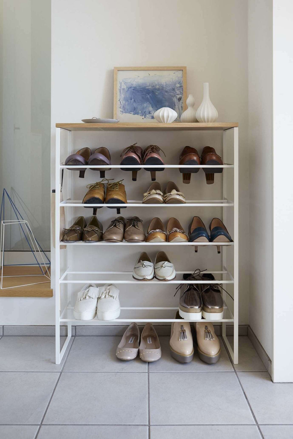 Straight-on view of Yamazaki's 6 Tier Wood Top Shoe Rack filled with shoes and household items, sitting next to a doorway on a tile floor.