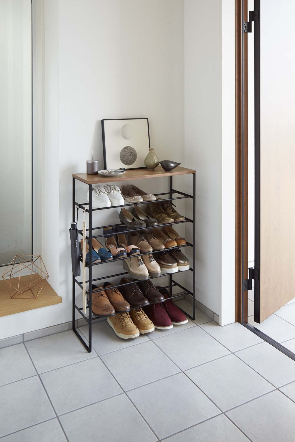 Yamazaki's Black 6 Tier Wood Top Shoe Rack filled with shoes on top of a tile floor