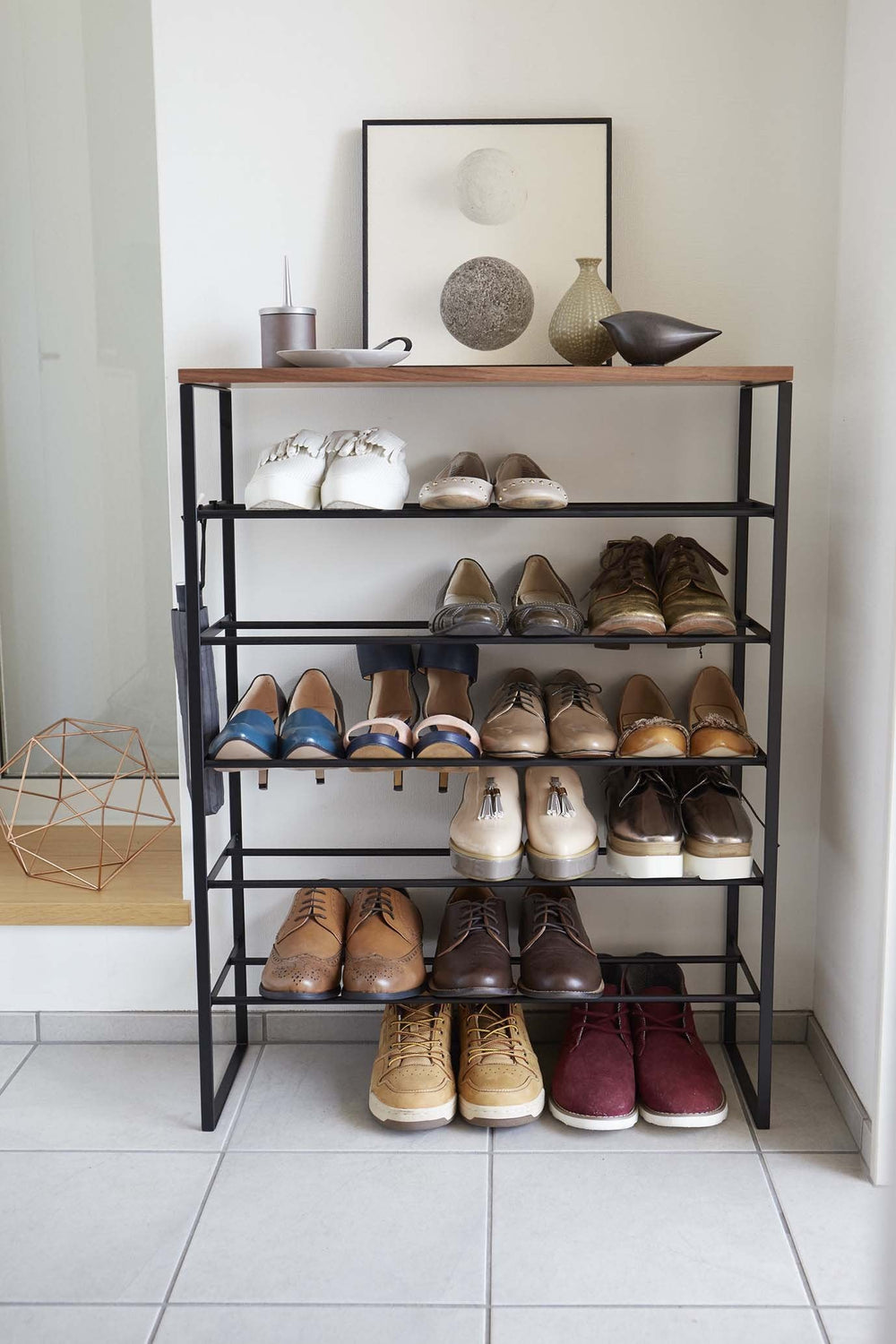 Straight-on view of Yamazaki's black 6 Tier Wood Top Shoe Rack filled with shoes and household items, sitting next to a doorway on a tile floor.
