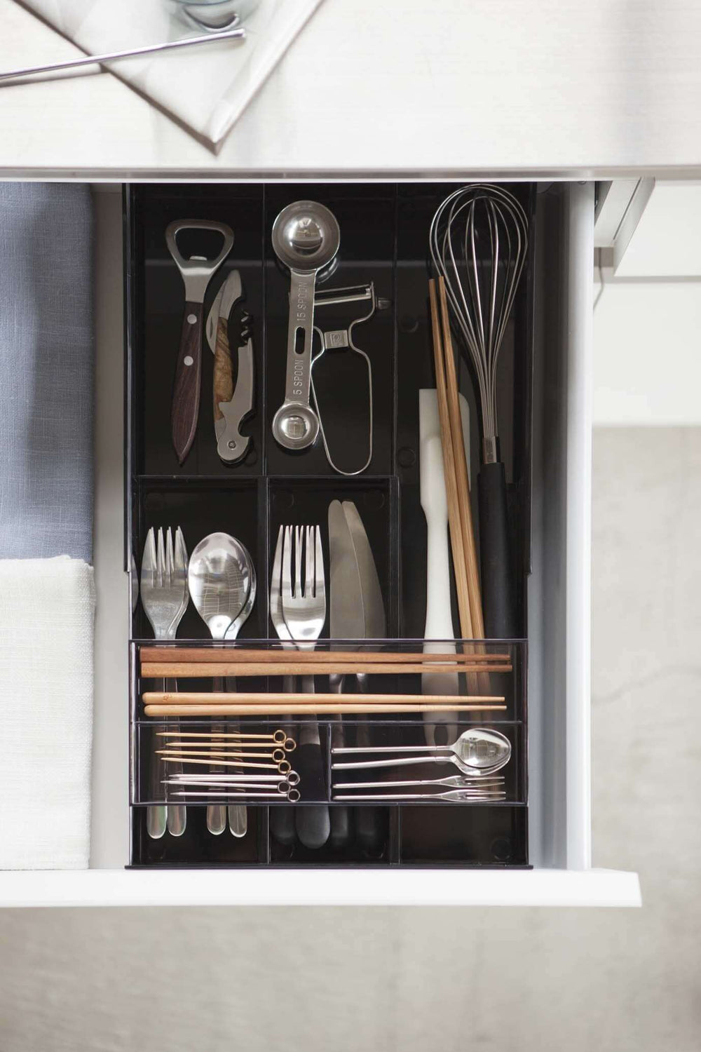 Yamazaki's black organizer filled with cutlery inside a kitchen drawer.