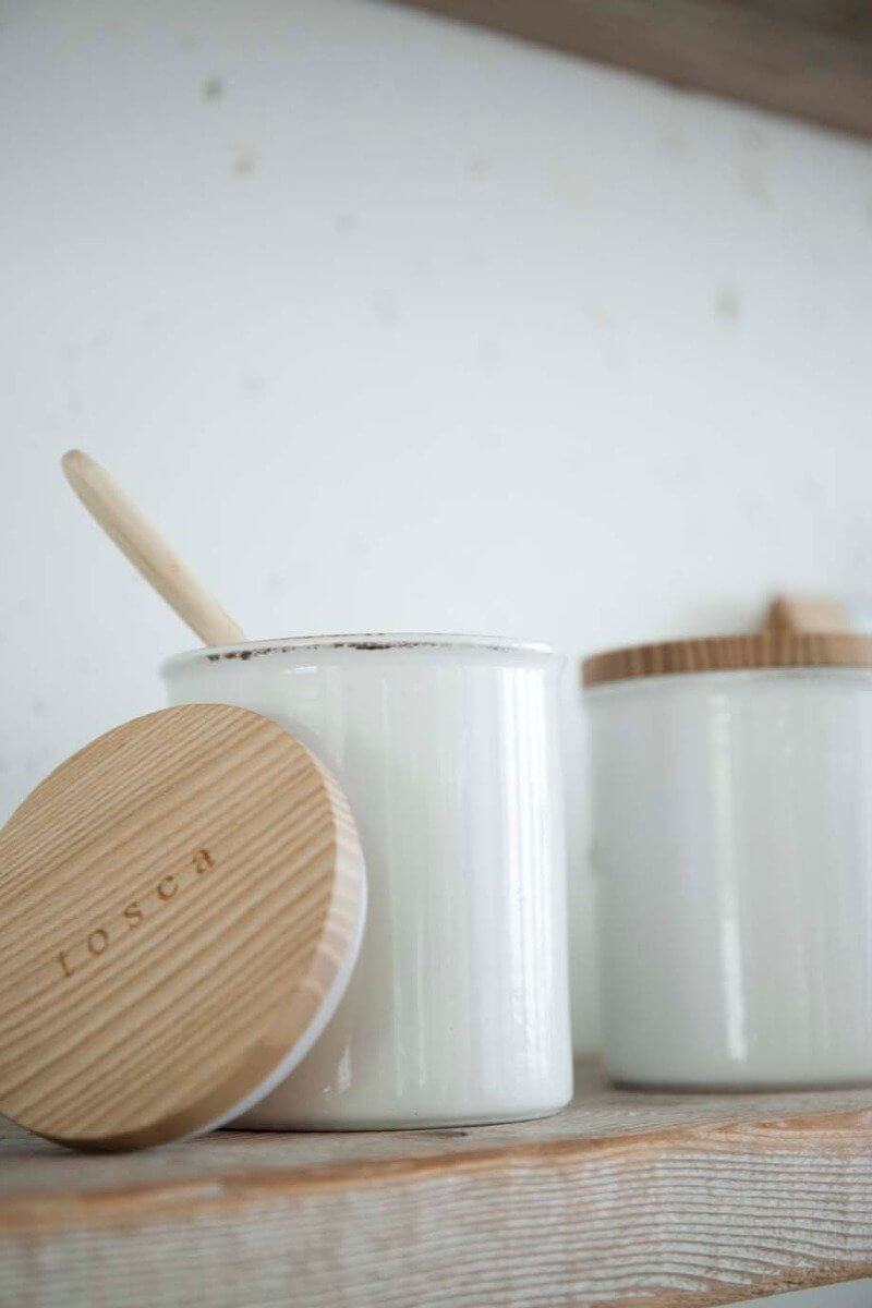 Two white Yamazaki ceramic canisters with wooden lids lined up on a kitchen shelf