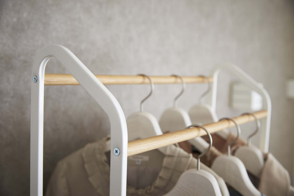 Hangers on the wooden rods of Yamazaki's rolling garment rack.
