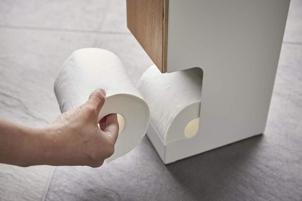 Someone removing a roll of toilet paper from the Yamazaki dispenser