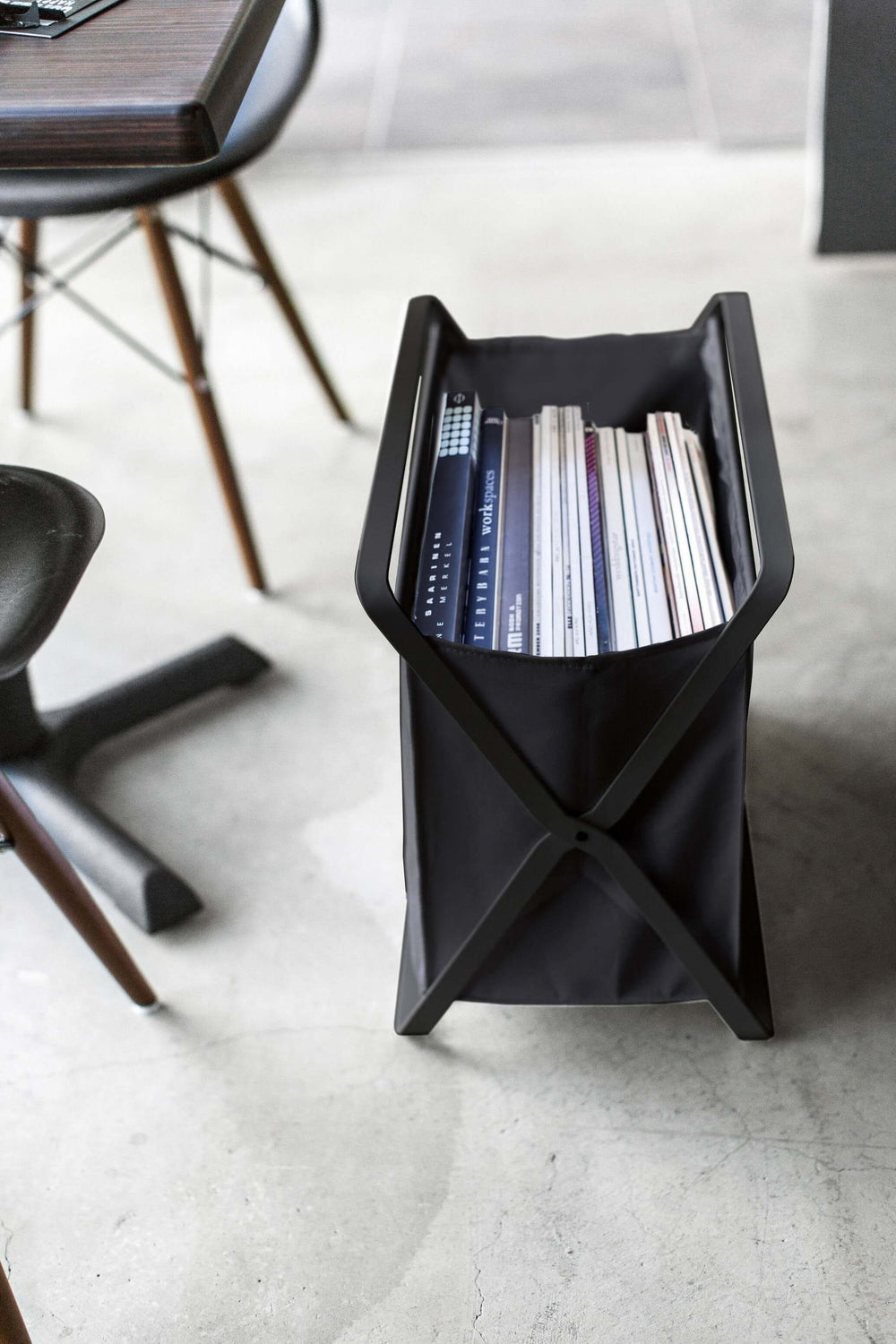 Black Yamazaki Storage Hamper next to a table and chair, storing books and magazines