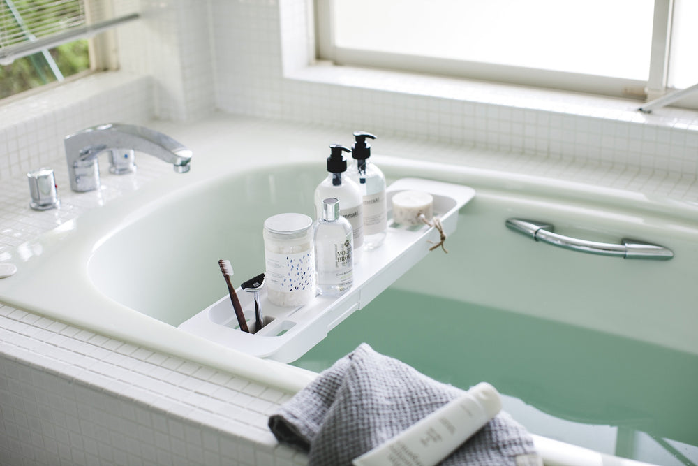 Yamazaki Bathtub Caddy in white expanded to fit over a filled bathtub, holding various bath products