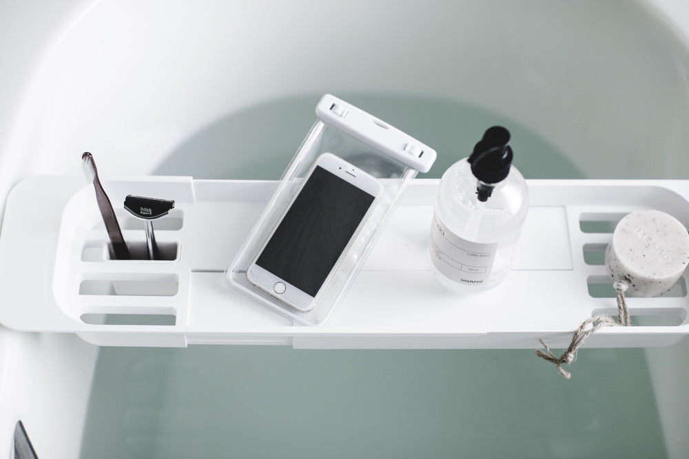 Aerial view of Bathtub Caddy in white over a filled bathtub, holding bath products and an iphone