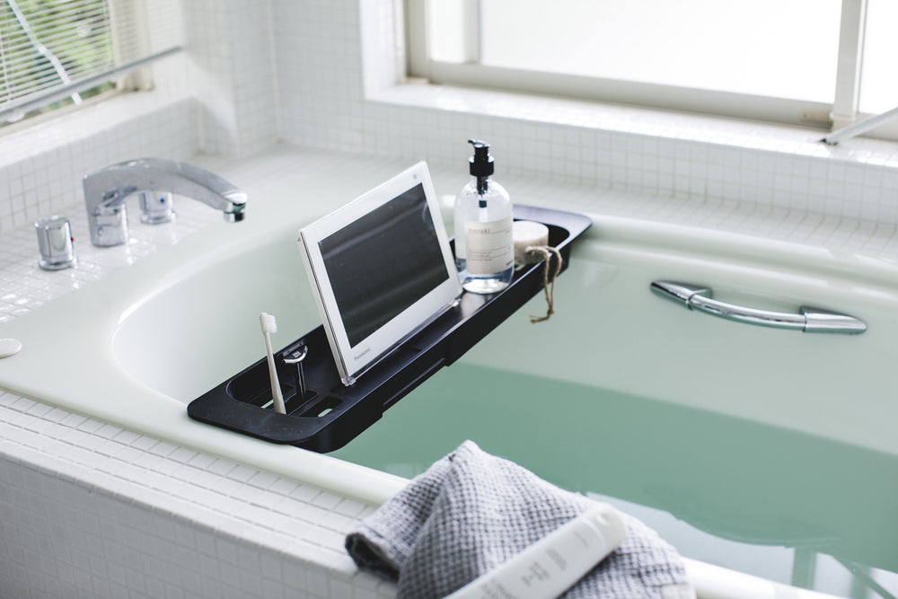 Yamazaki Bathtub Caddy in black, over a filled bathtub, holding bath products and a tablet