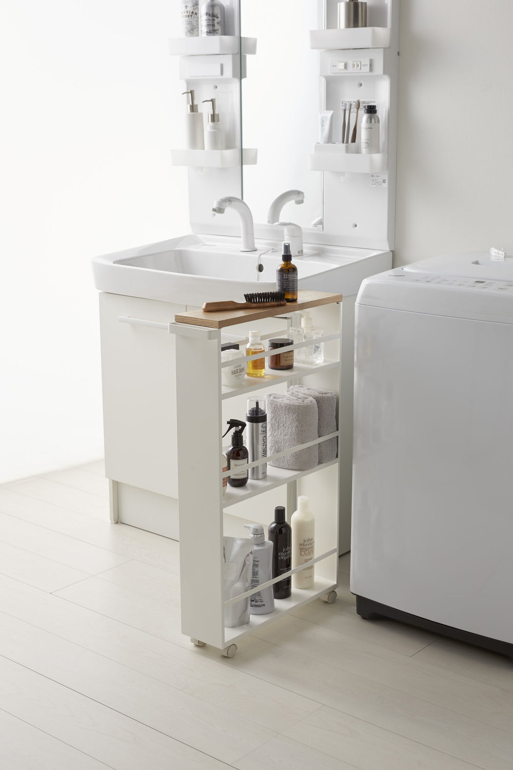 The Yamazaki Rolling Slim Storage Cart, stocked with bathroom items, between a sink vanity and appliance in a modern bathroom