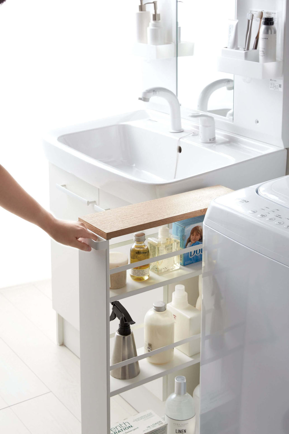 Person easily rolling the Yamazaki Slim Storage Cart out from between the bathroom vanity and appliance