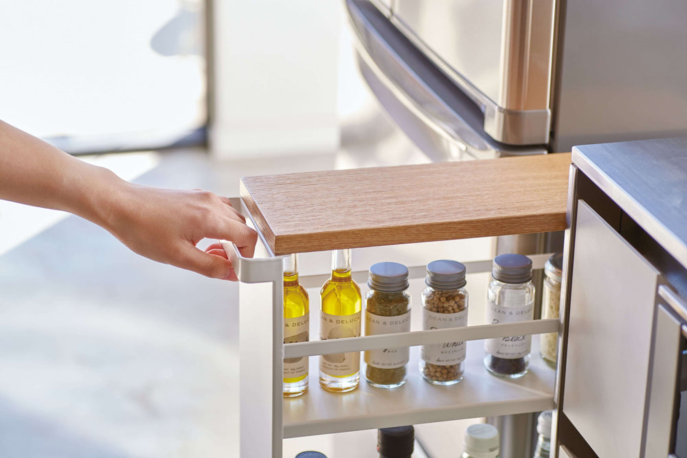 Person pulling a stocked Yamazaki slim storage cart from its storage space in the kitchen
