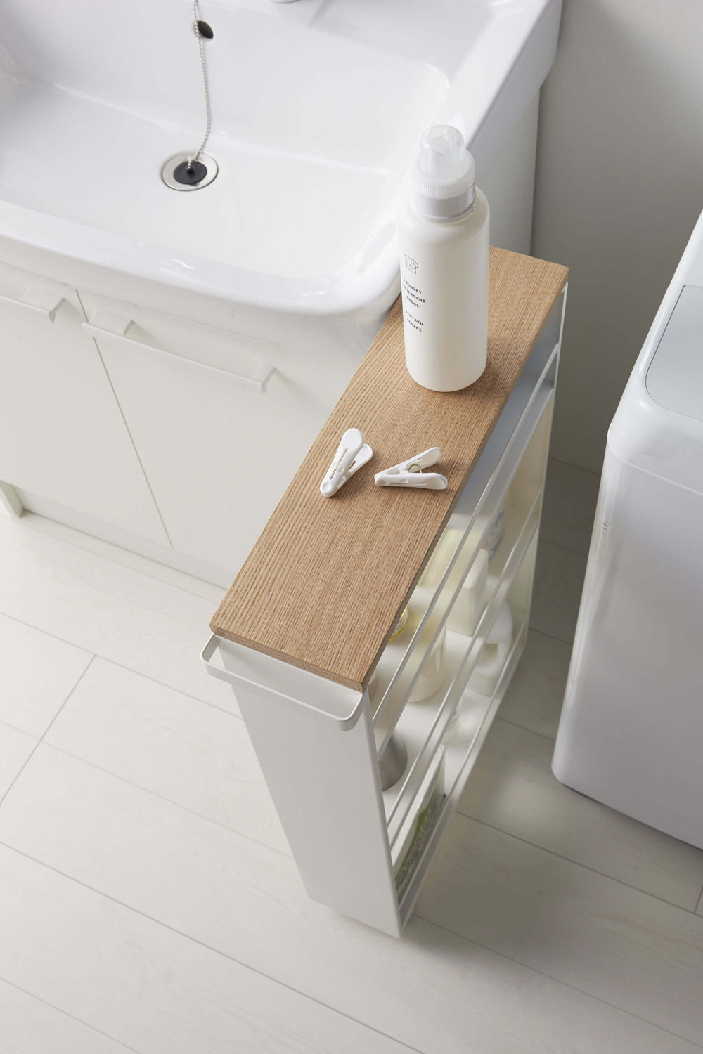 Aerial view of the Yamazaki Rolling Slim Storage Cart with bathroom spray and clips resting on the wooden top
