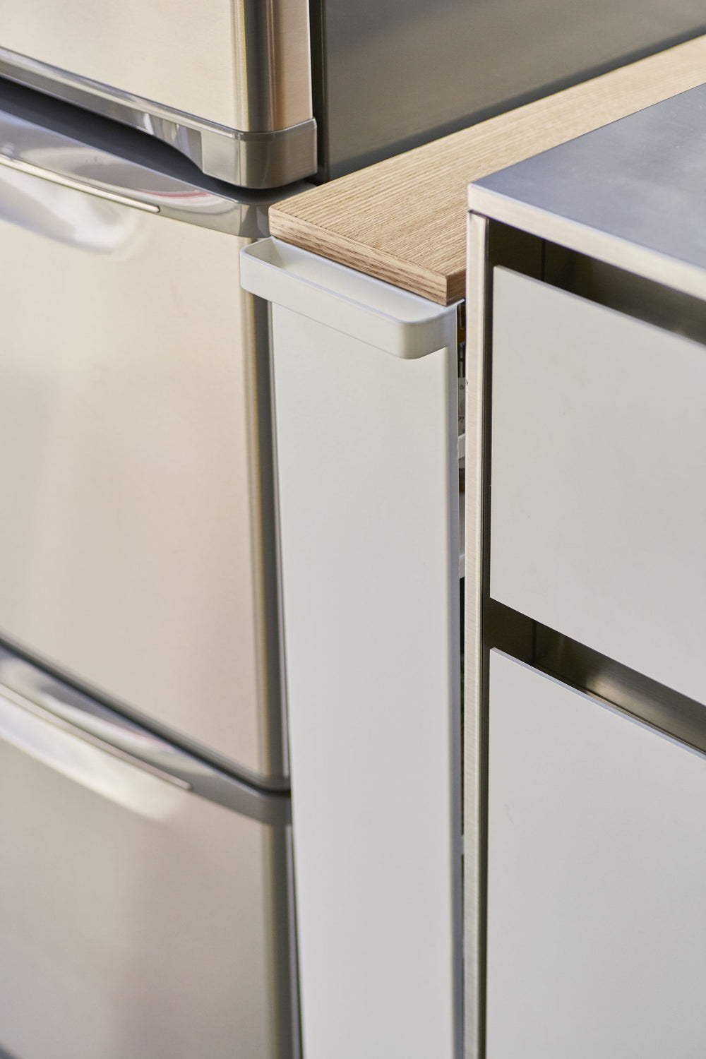 Close up of the Yamazaki Rolling Slim Storage Cart tucked seamlessly between a refrigerator and countertop, with handle facing outward