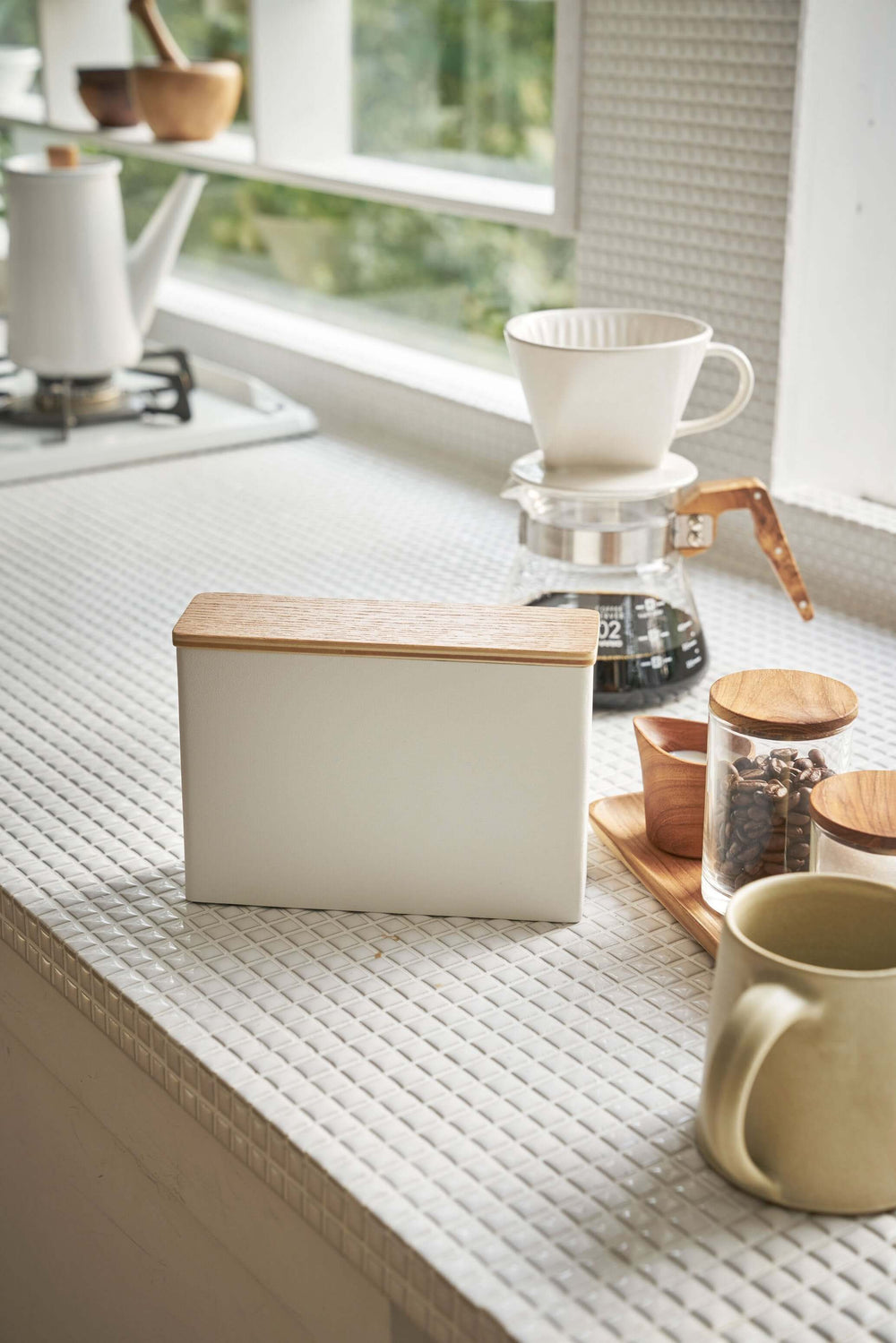 Yamazaki Wood-Accent Coffee Filter Case sitting closed on a white tile kitchen countertop, with coffee-making items