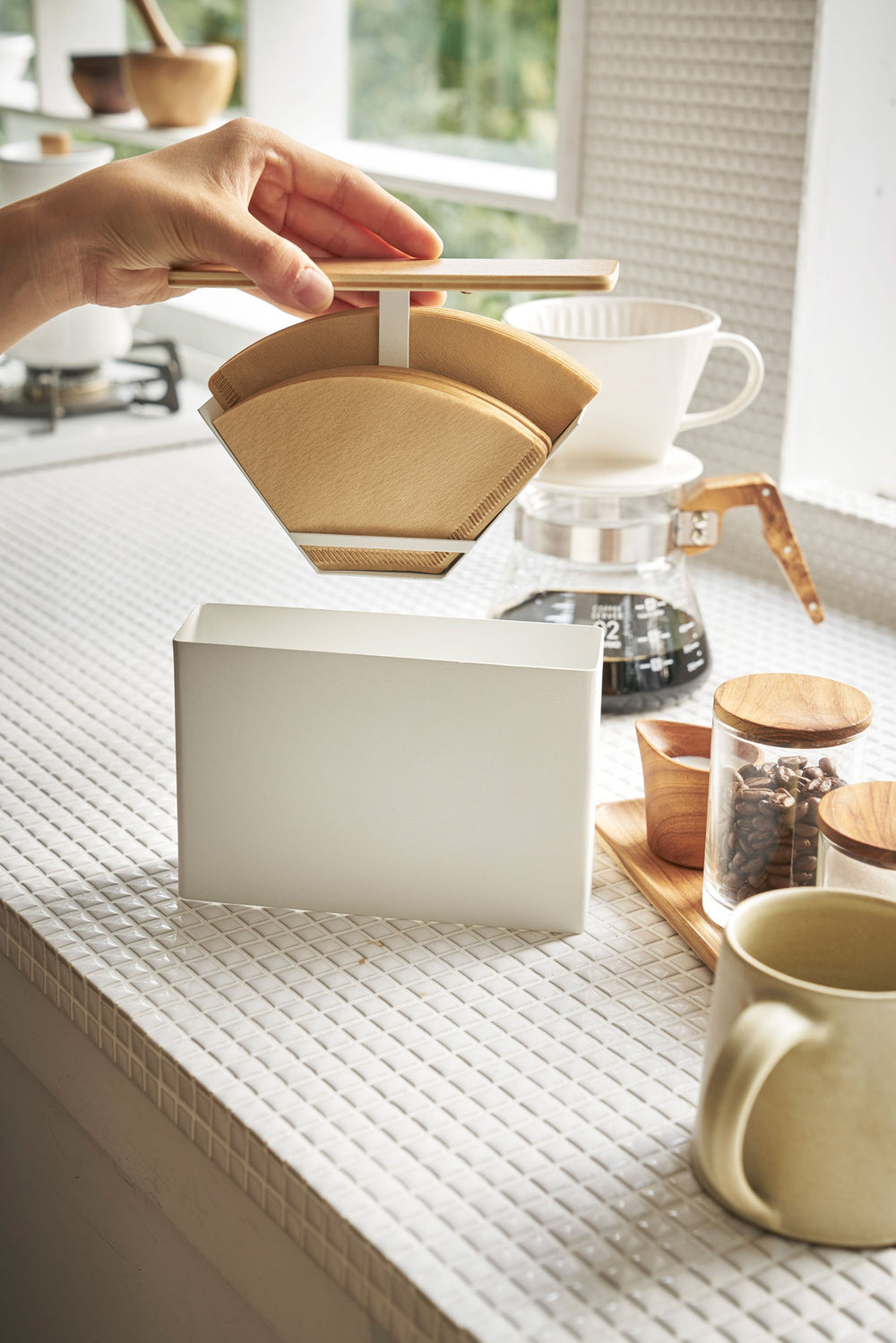 Person lifting the filters from the Yamazaki Coffee Filter Case as it sits on a countertop, surrounded by coffee making items