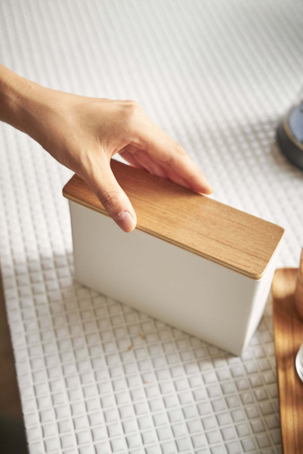 Person with their hand on the wooden top of the Yamazaki Coffee Filter Case