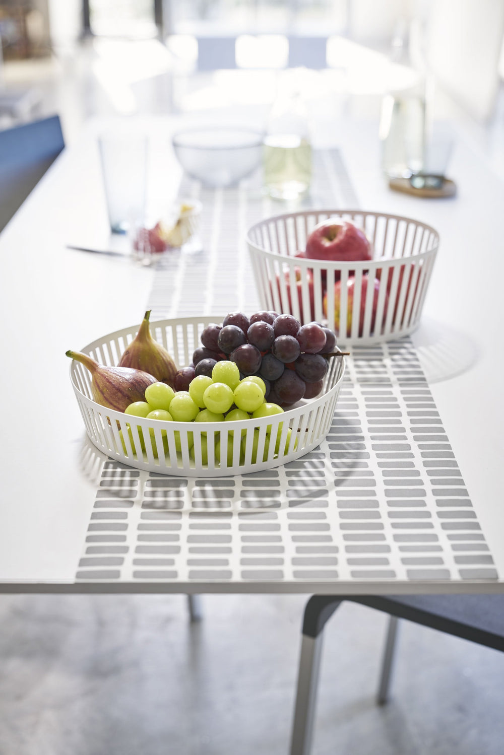 Short and tall Yamazaki Striped Steel Fruit Baskets, holding grapes and apples on a set dining room table
