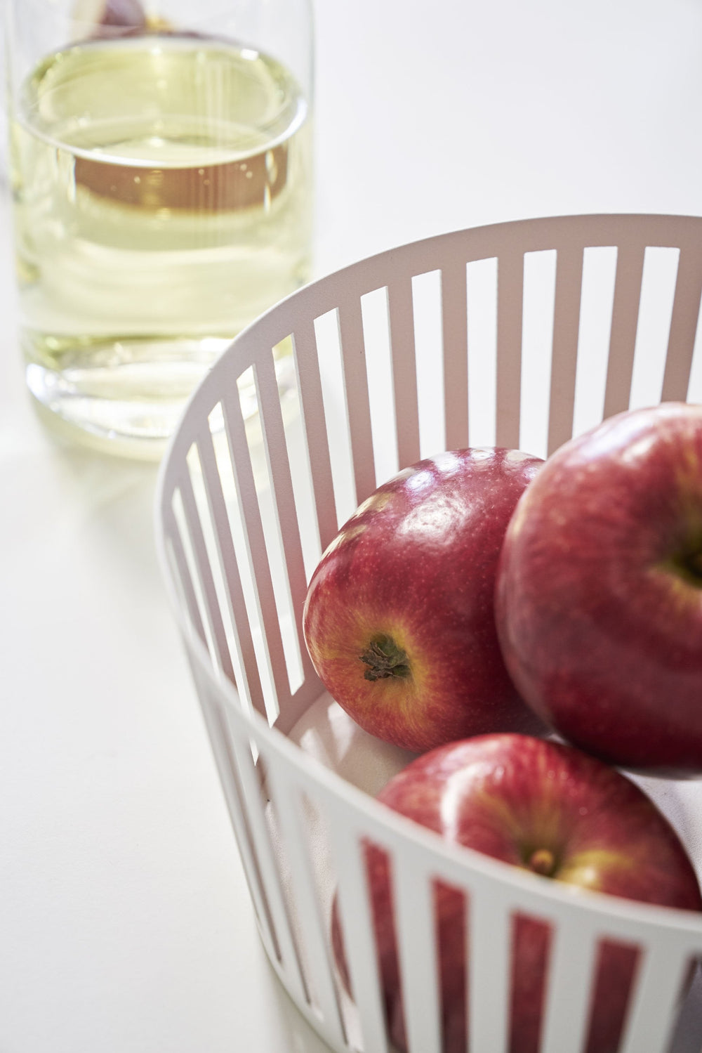 Detail view of apples in a white Yamazaki Striped Steel Fruit Basket