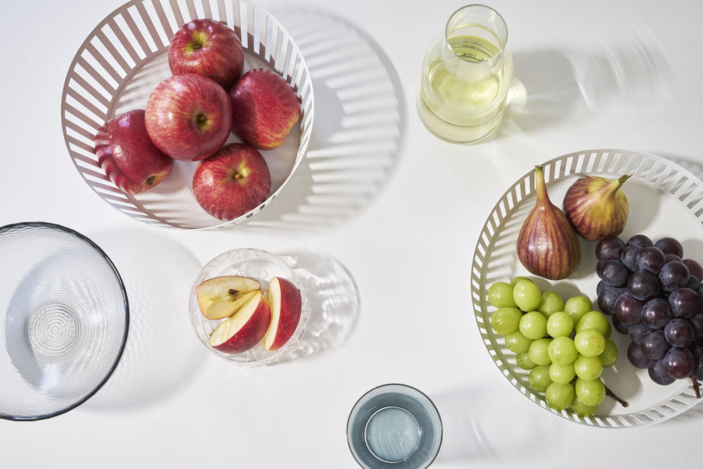 Aerial view of two white Yamazaki Striped Steel Fruit Baskets on a table, holding apples and grapes